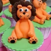 Green cupcakes with orange and brown lion toppers
