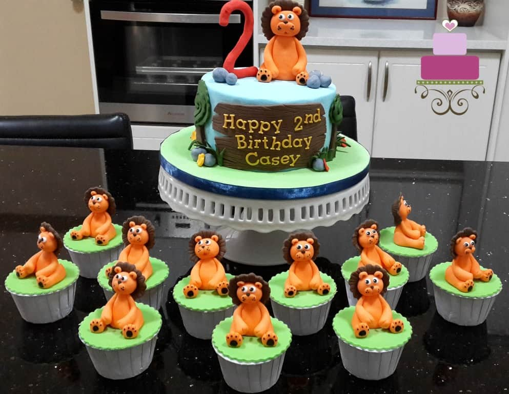 A round cake with a large lion topper and green cupcakes with orange and brown lion toppers