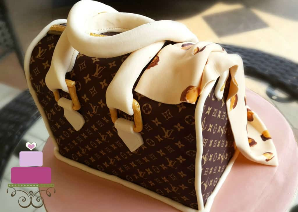 A Louis Vuitton inspired handbag cake with a leopard print scarf and edible pearl necklace