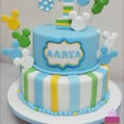 A 2 tier cake decorated with Mickey face cut outs in blue, white, green, yellow and white and a matching number 1 topper