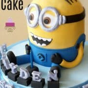 A Minion shaped birthday cake with silver alphabets on a blue cake board