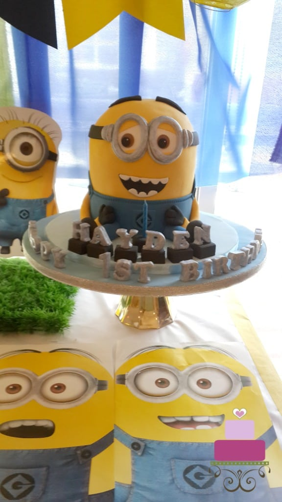 A Minion shaped birthday cake with silver alphabets on a blue cake board.