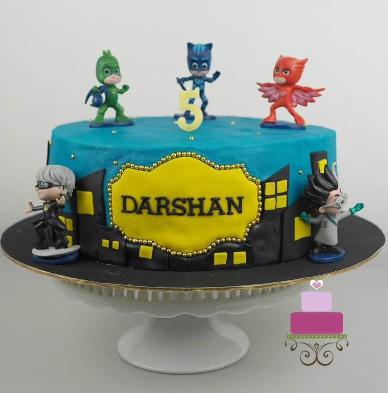 A round cake in blue with PJ Masks characters cake toppers