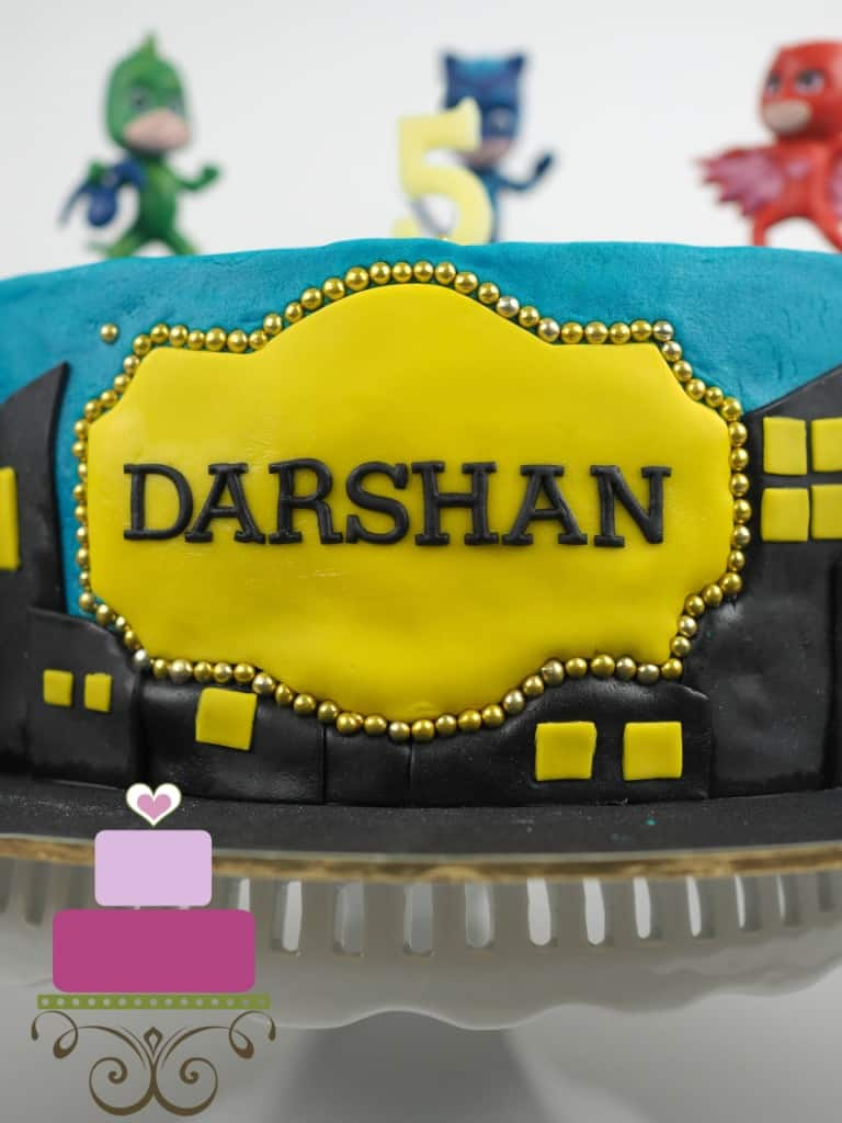 Yellow fondant plaque with wordings Darshan in black. Plaque is framed with gold beads