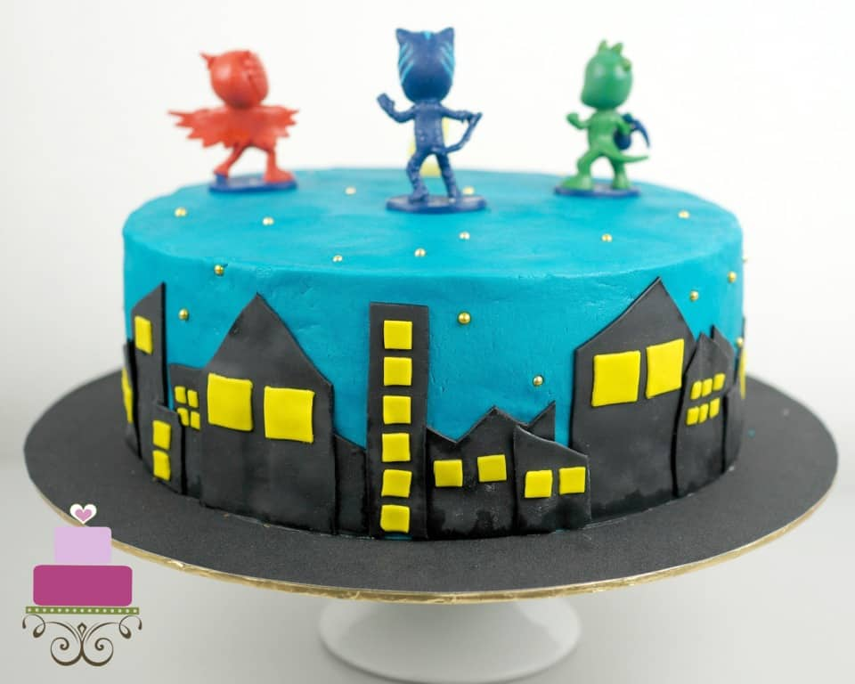 Fondant buildings in black and yellow on a blue cake with PJ Masks toppers