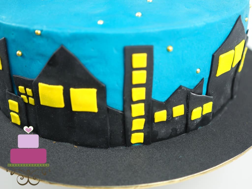 Fondant building in black and yellow on a blue cake
