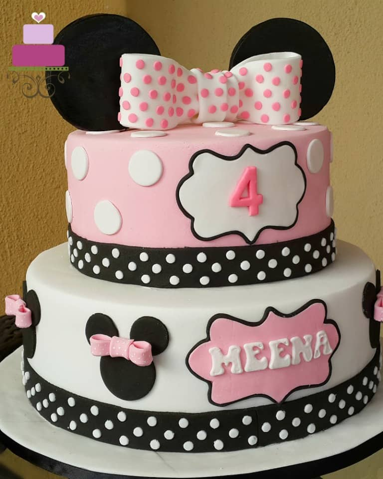 A 2 tier pink Minnie Mouse themed birthday cake with a large pink polka dots topper
