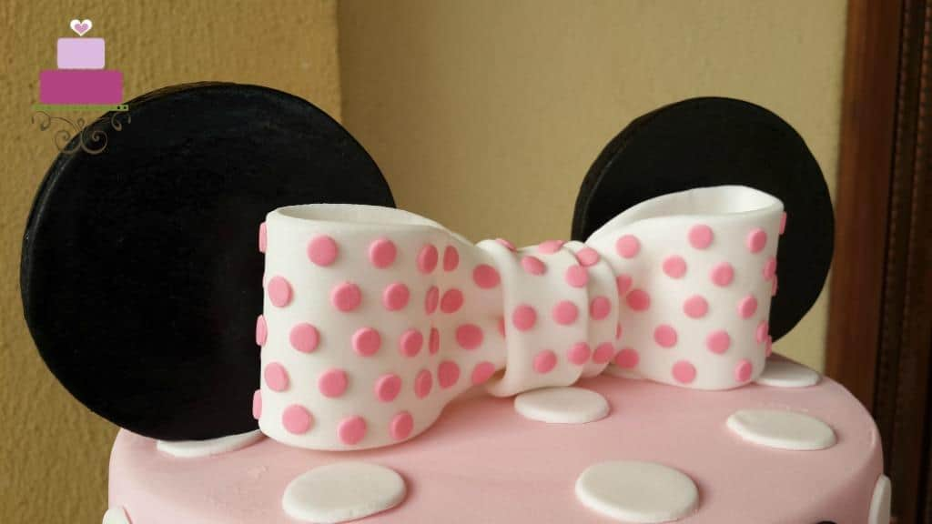 A large white bow with pink polka dots on a pink cake