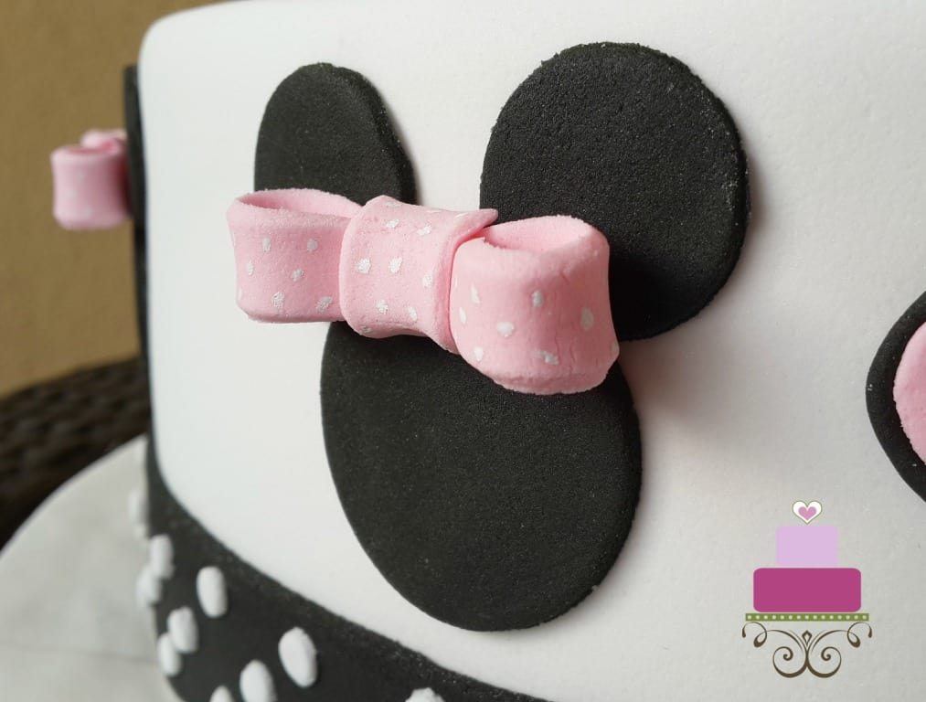A Minnie face cut out in black wiht a 3D pink bow attached