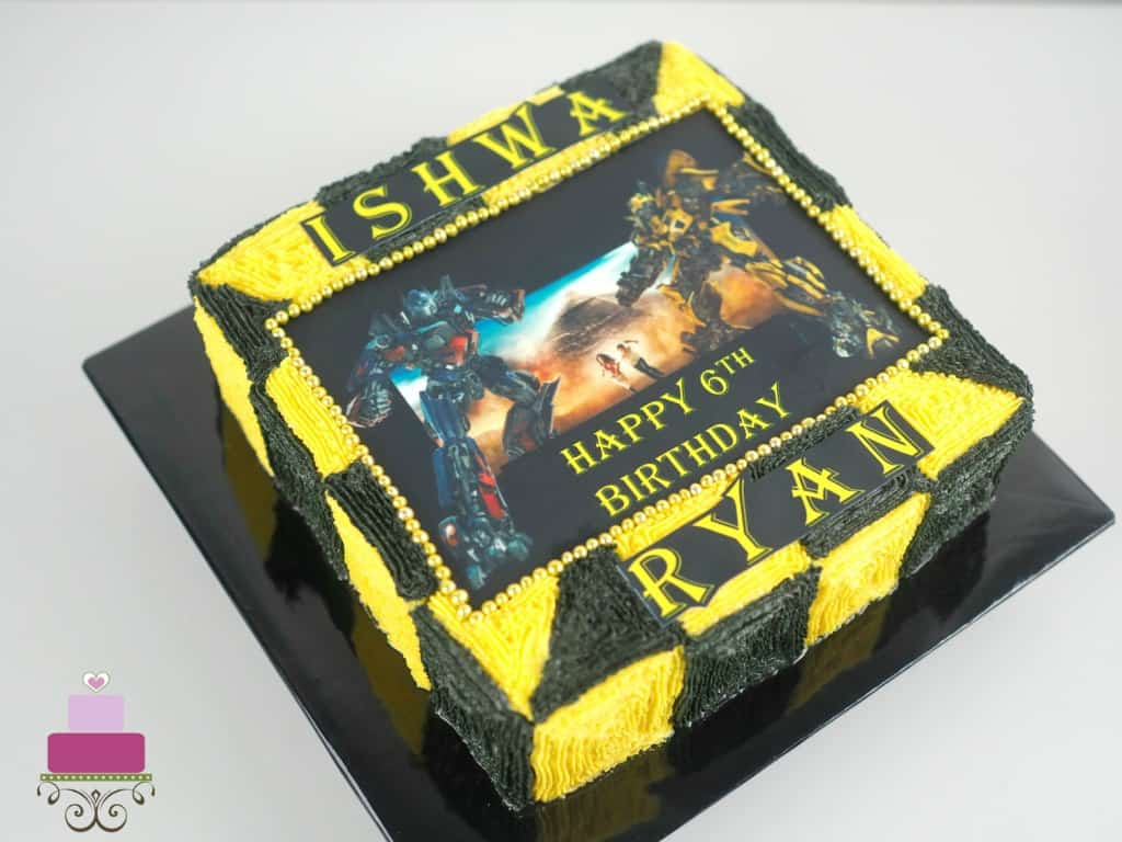 A square cake decorated with yellow and black buttercream squares and Transformers edible image