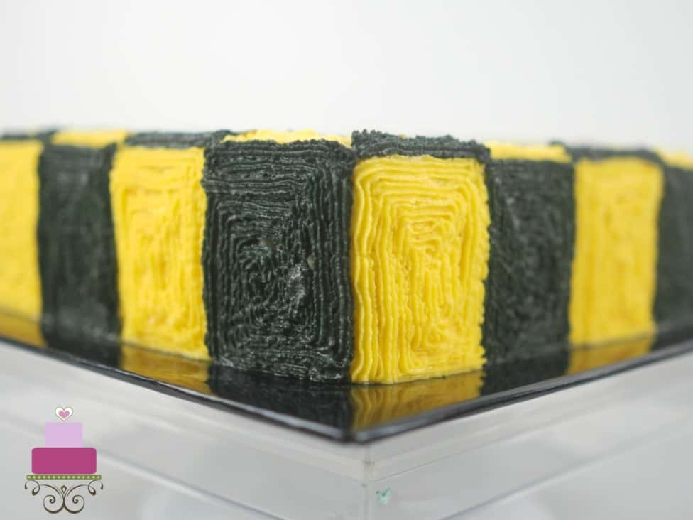 The sides of a cake decorated with yellow and black buttercream squares