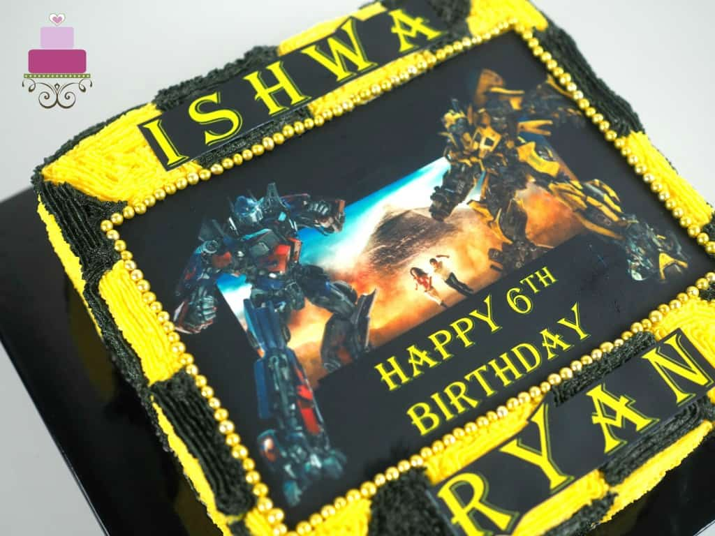 A square cake decorated with Transformers edible image and yellow and black buttercream