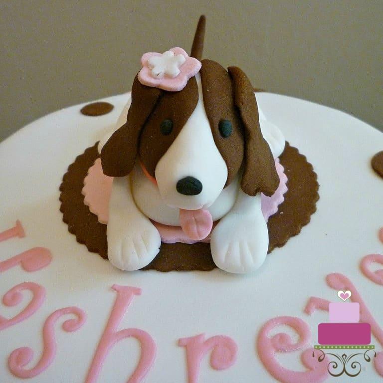 A fondant dog topper on a round cake