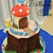 A mushroom on a tree stump cake decorated in Smurfs theme. A 3D Smurf in fondant is the cake topper