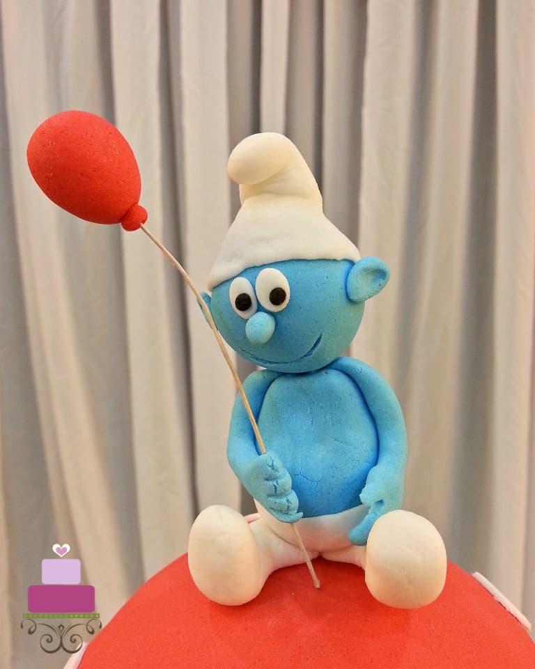 3D fondant Smurf topper holding a red ballon
