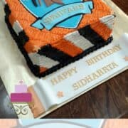 A square cake with orange, black and white side strips and a Spartans logo