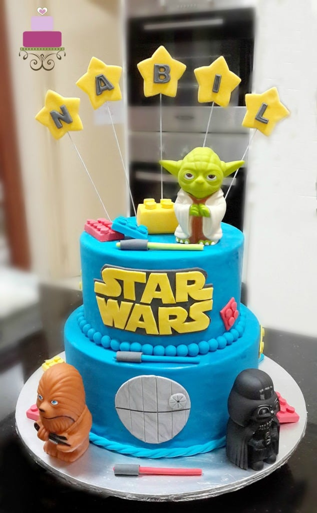 A 2 tier round cake decorated in blue. Cake is topped with figurines from Star Wars Lego.
