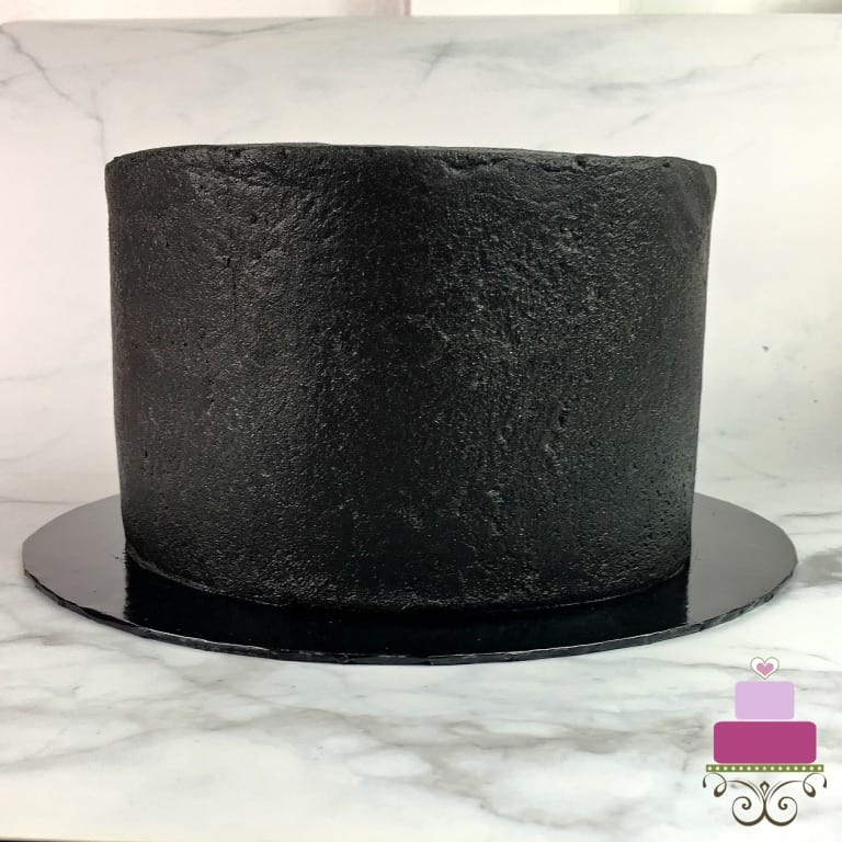 A round cake covered in black icing