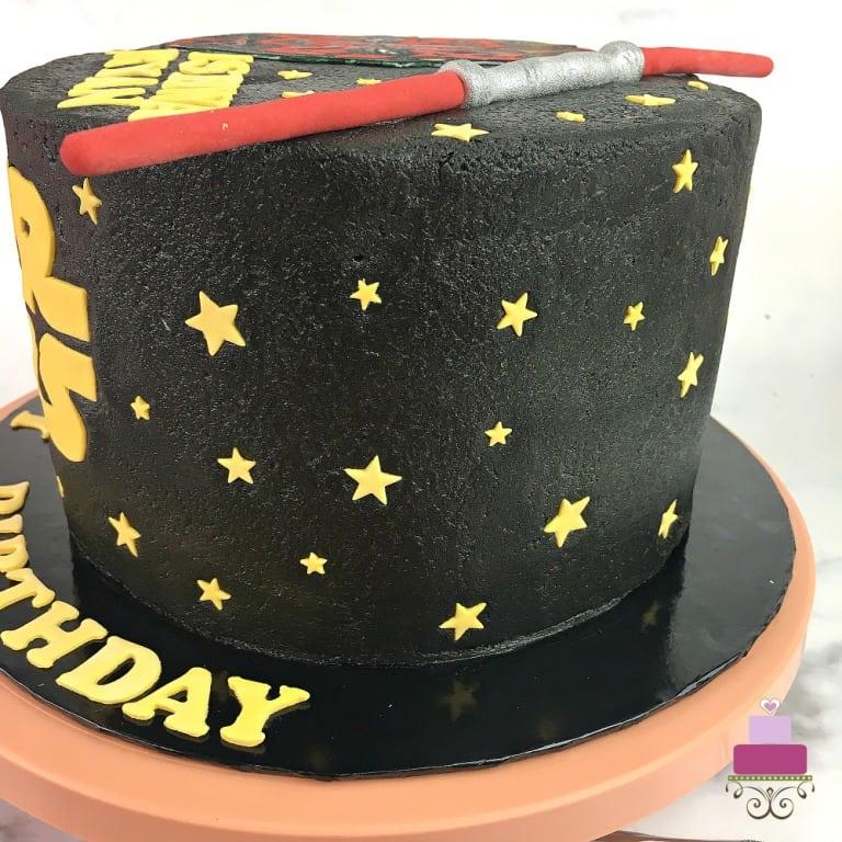 Tiny yellow fondant stars on a black Star Wars birthday cake