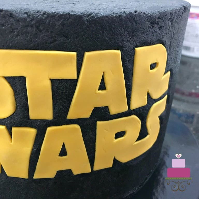 Star Wars logo in yellow fondant on the front of a cake