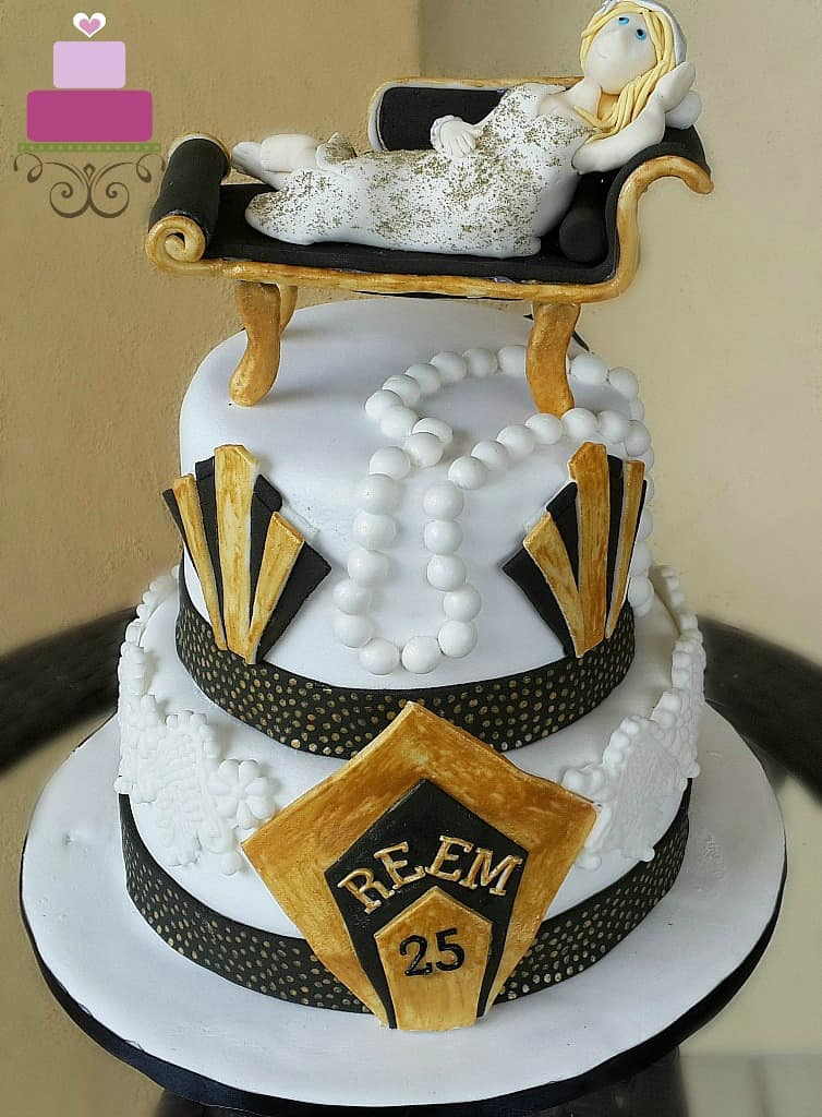 A two tier cake in black, white and gold with a lady figurine lying down on a couch.