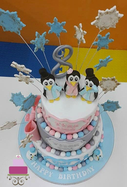 A 3 tier cake in blue, silver and pink and 3 cute penguins toppers.