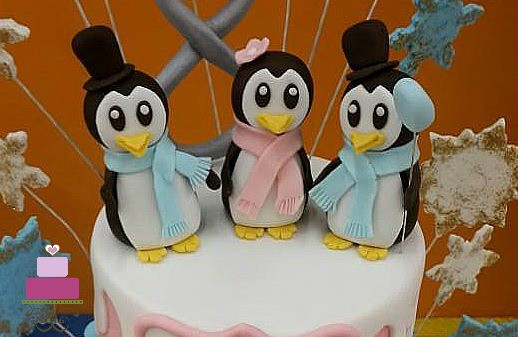 3 penguin toppers on a cake