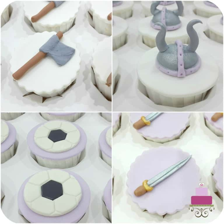 A set of cupcakes decorated with viking helmets, swords, axes and footballs