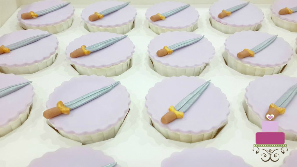Purple cupcakes with sword toppers