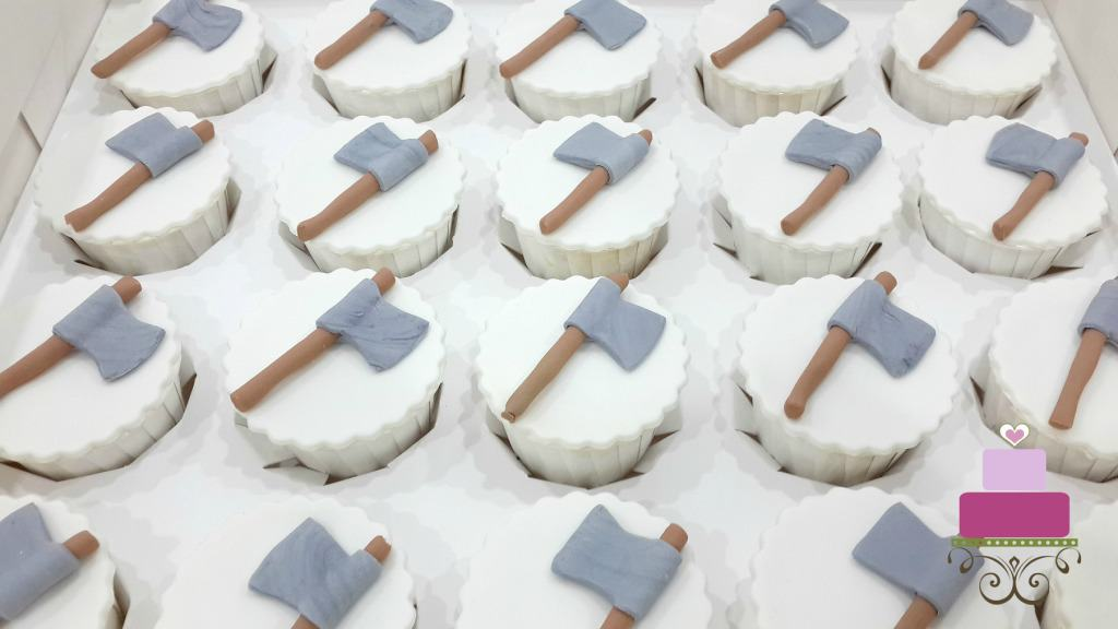 White cupcakes with fondant axe toppers