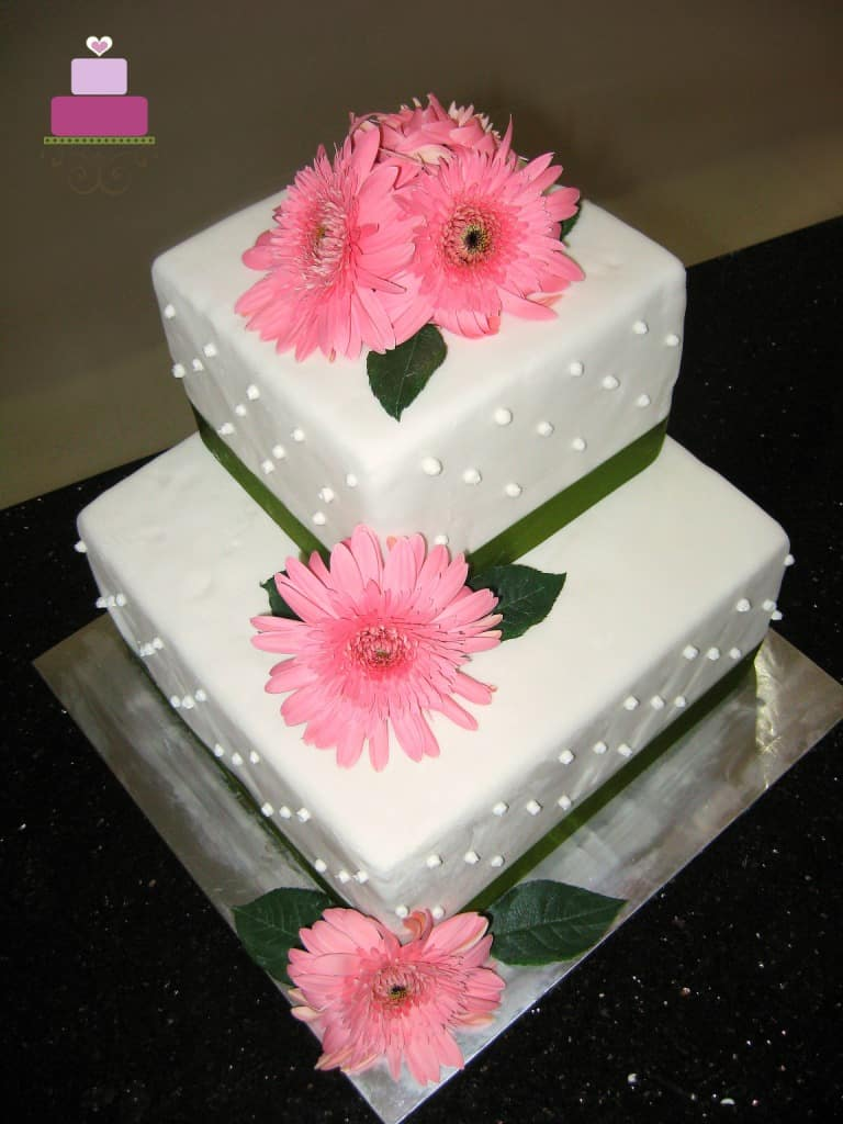 A 2 tier square wedding cake decorated with green ribbon border and fresh pink gerbera flowers