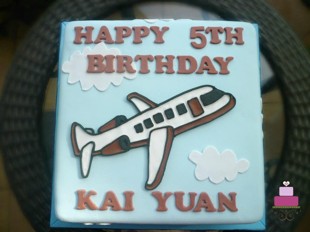 A square cake with an airplane motif on it.