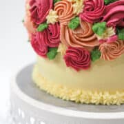 Buttercream cake decorated with buttercream flowers, on a white cake stand