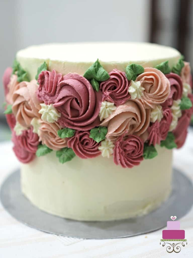 Round cake decorated with pink buttercream rosettes