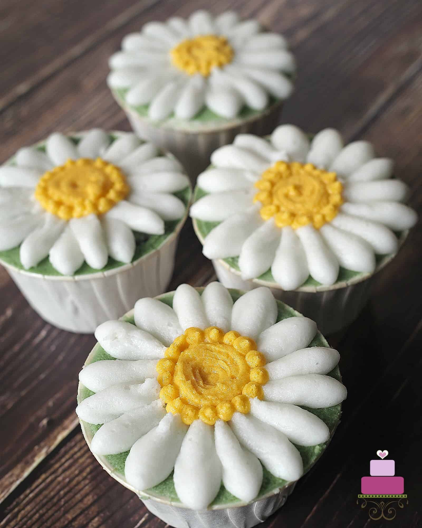 4 daisy cupcakes against a wood background