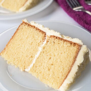 Two slices of white cake on a white plates. Cakes consist of 2 layers sandwiched and covered in buttercream