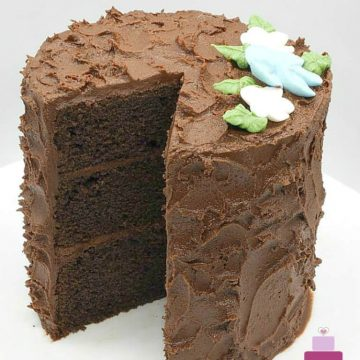 A round chocolate cake decorated with chocolate icing and royal icing flowers. A slice of the cake is cut out