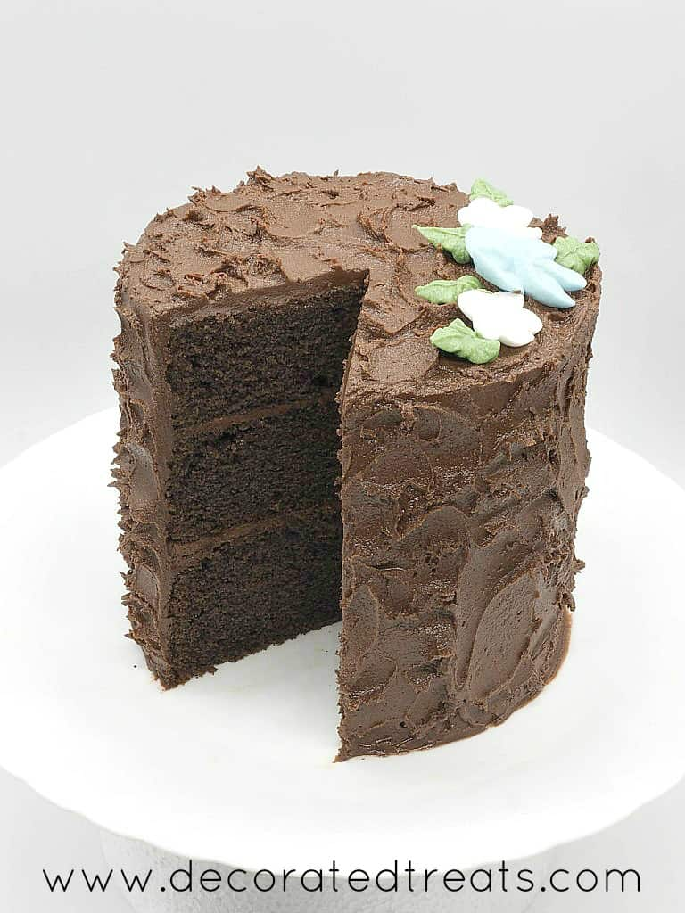 A round chocolate cake covered in chocolate icing and decorated with royal icing flowers
