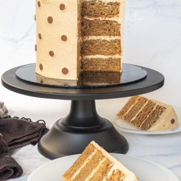 A round cake decorated with polka dots icing. Cake is in a black cake stand with a slice cut onto a white plate