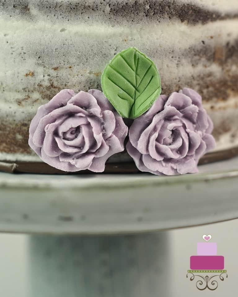 2 purple roses on the sides of a cake