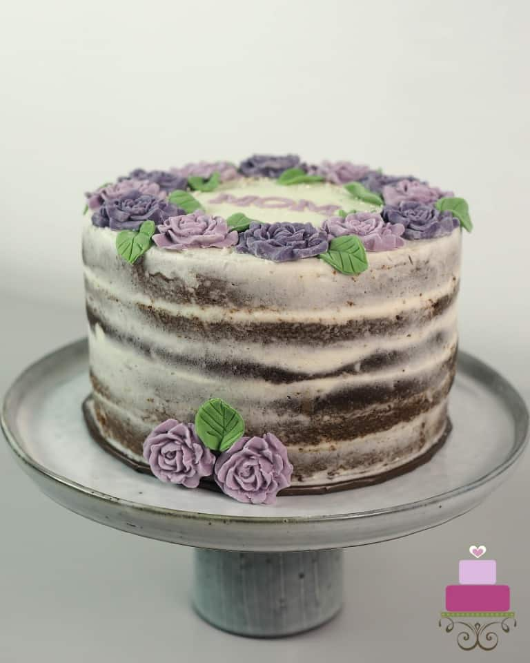 A round cake decorated with purple and violet roses