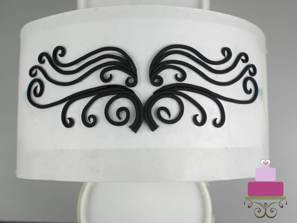 Black fondant swirl pattern on a paper template