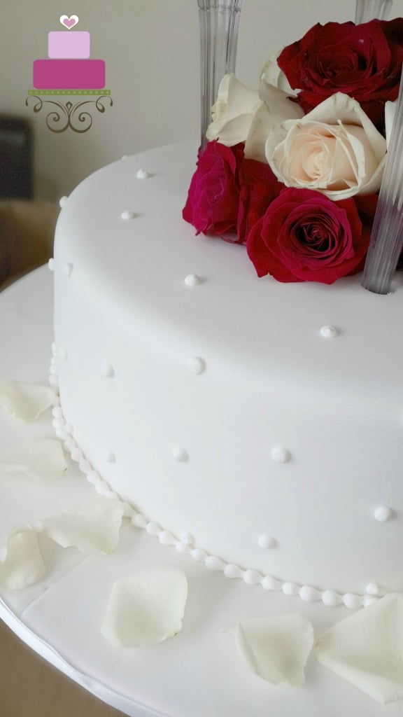 A white wedding cake decorated with fresh maroon and champagne roses