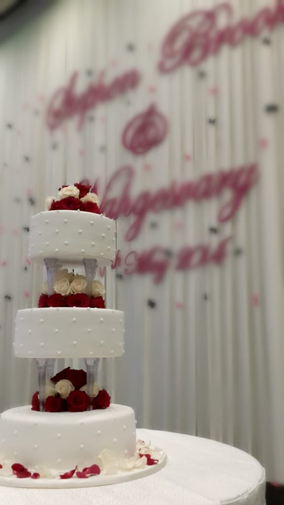 3 tier wedding cake on pillars, decorated with fresh red and champagne colored roses