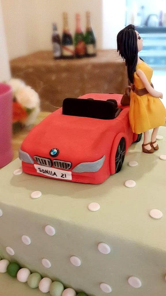 A square green polka dots cake with a stylist lady figurine and a BMW car cake topper.