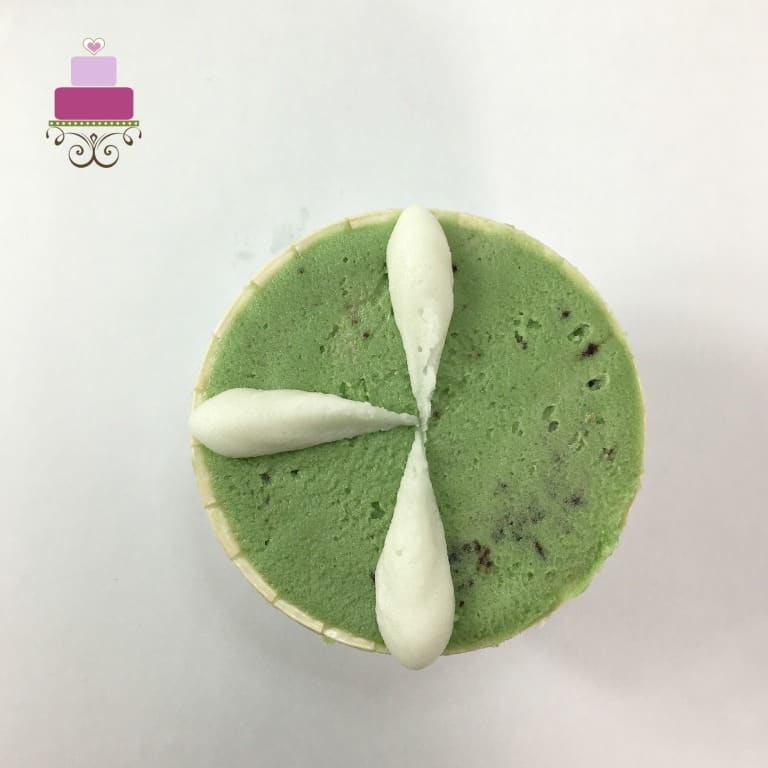 3 white petals on a green buttercream covered cupcake