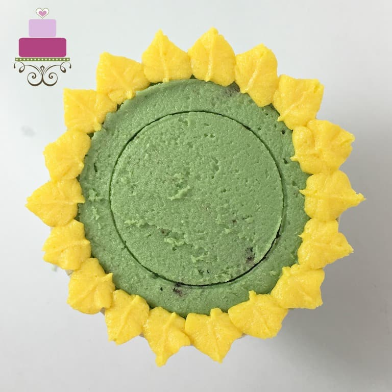 A layer of yellow petals on a green icing covered cupcake