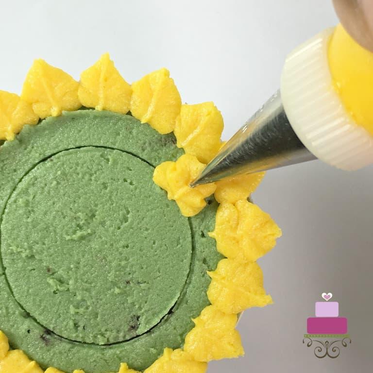 Piping yellow petals on a green cupcake