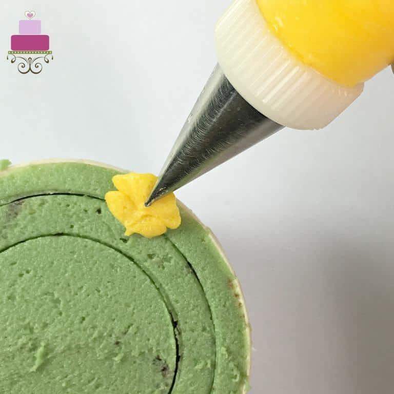Piping a yellow petal on a green cupcake