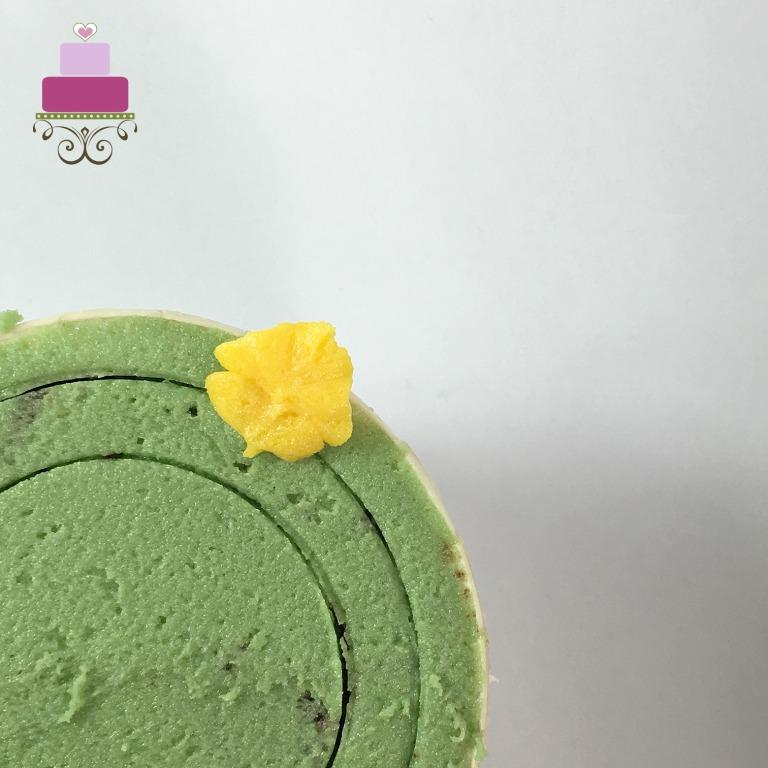 A yellow petal on a green cupcake